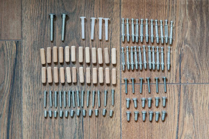 顶视图安排小组零件定缝销钉,螺栓,家具汇编的螺丝在木地板上 为装配家具的工具 d 库存图片