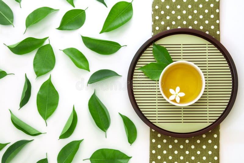 顶视图射击了一杯热的茶与绿色叶子装饰的  免版税库存照片