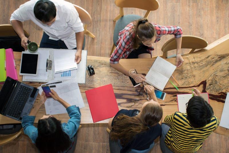 顶视图小组少年的朋友忙于工作在与报告的队和膝上型计算机在大学 免版税库存照片