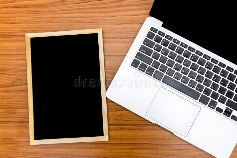 顶视图小黑板和膝上型计算机在与纹理的木背景投入了 在黑板的自由空间文本输入的 免版税库存图片