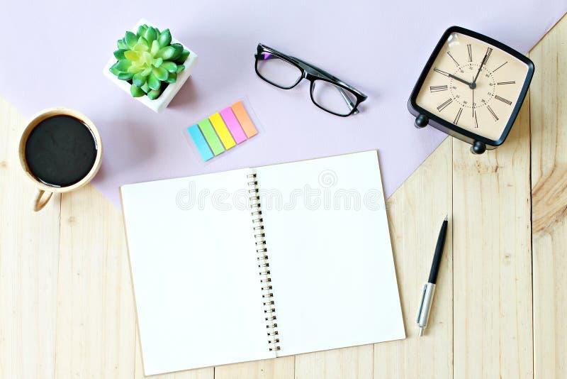 顶视图或开放笔记本纸平的位置与空白页、辅助部件和咖啡杯的在木背景,为增加准备或 免版税库存图片
