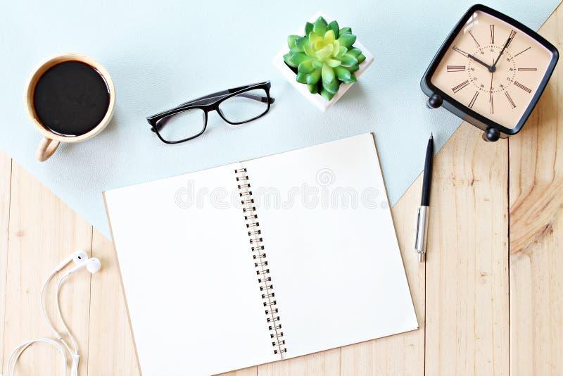 顶视图或开放笔记本纸平的位置与空白页、辅助部件和咖啡杯的在木背景,为增加准备或 免版税库存照片