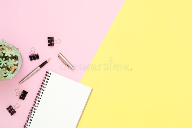顶视图有开放嘲笑的办公桌笔记本和铅笔和植物桃红色黄色淡色背景的 库存图片