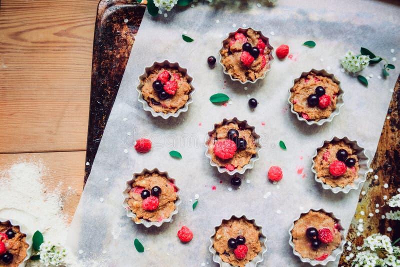 顶视图未加工的面团用杯形蛋糕的莓果分解了入在烘烤papper的形式在烘烤盘子装饰的ewith花 Sele 库存照片
