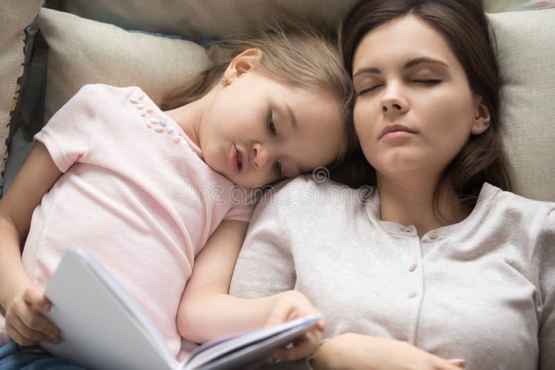 顶视图母亲睡着,当她的女儿看书时 免版税库存照片