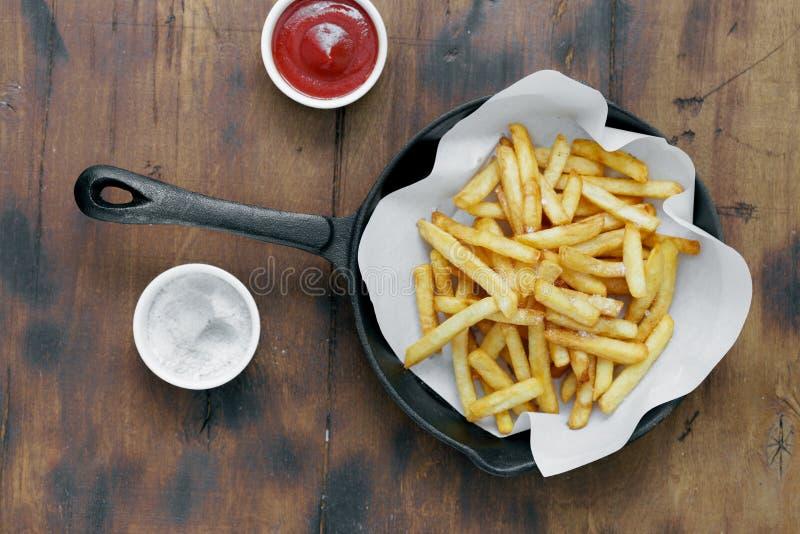 顶视图炸薯条供食了煎锅木桌番茄酱 图库摄影