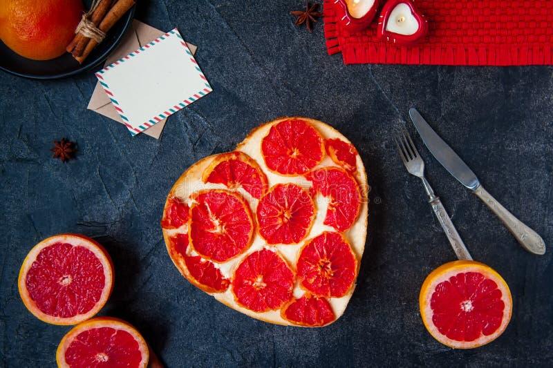 顶视图烘烤了与红色葡萄柚切片的乳酪蛋糕以在黑石背景的心脏,愿望的明信片, fre的形式 库存图片