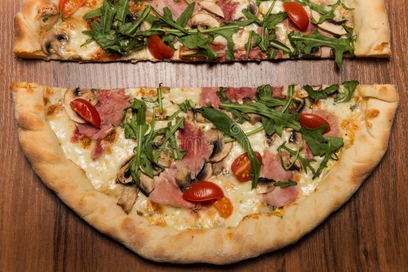 顶视图特写镜头两一半与芝麻菜、火腿和蕃茄的比萨 免版税图库摄影