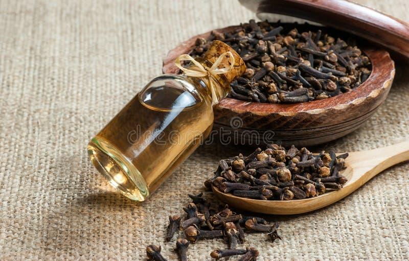 顶视图玻璃瓶丁香油和丁香在木匙子和碗在粗麻布大袋 免版税图库摄影