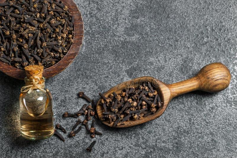 顶视图玻璃瓶丁香油和丁香在木铁锹或匙子和碗在灰色土气桌上 库存图片