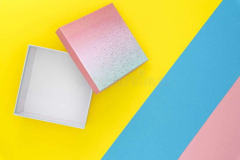 顶视图礼物盒开放在淡色蓝色,桃红色和黄色背景 生日礼物概念 最小五颜六色 免版税库存照片