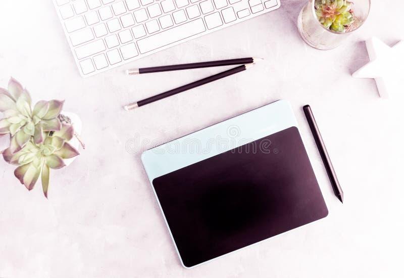 顶视图舱内甲板在灰色办公室桌放置图形输入板 现代设计师` s工作地点 免版税库存照片