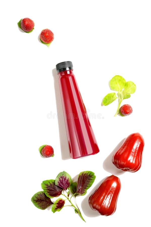 顶视图舱内甲板被放置的红色瓶汁液用在白色背景和蒲桃隔绝的菠菜、草莓 健康生活方式,v 免版税库存图片