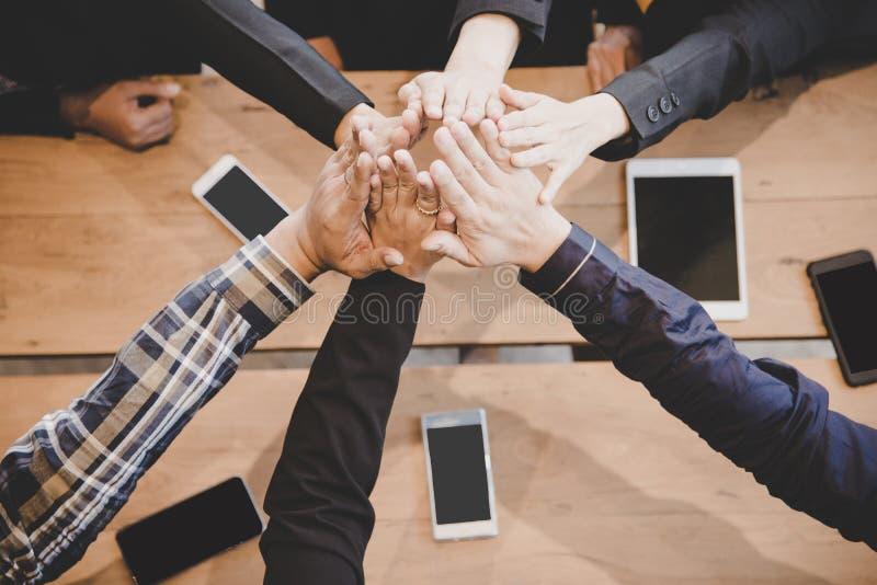 顶视图行政商人在遇见伙伴busine以后编组队愉快的显示的配合和加入的手或者给五 免版税库存照片