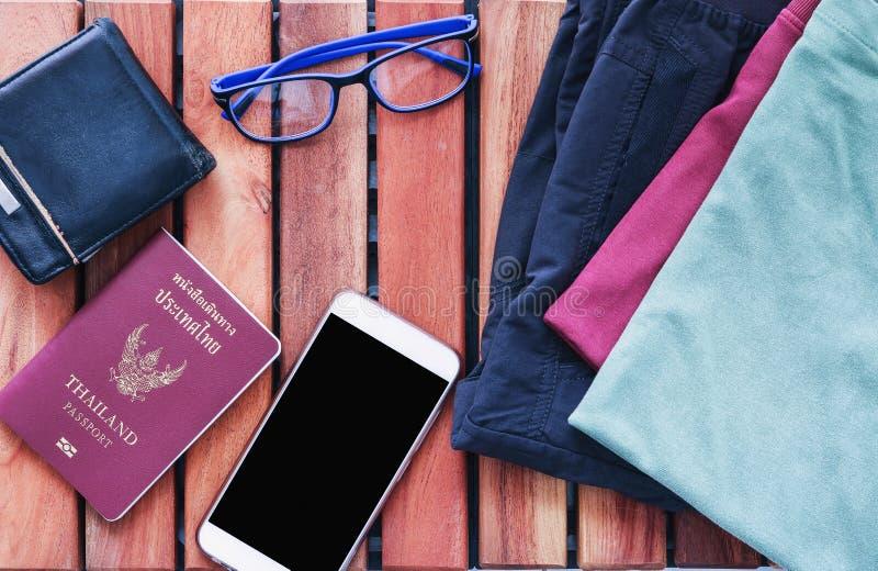 顶视图衣物和裤子旅客` s护照,钱包,玻璃 库存图片