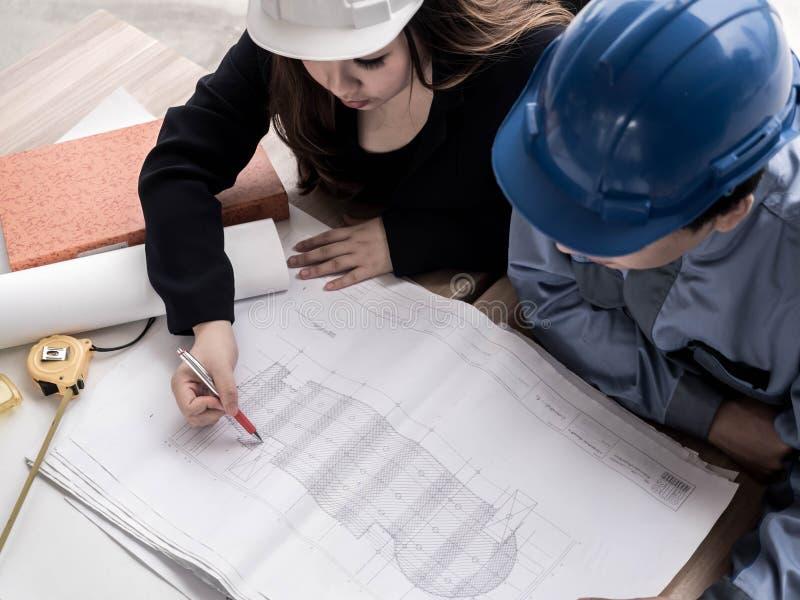 顶视图谈论配合概念、的工程师和的工作者新的大厦项目  建筑师亚裔人民队小组的 免版税库存照片