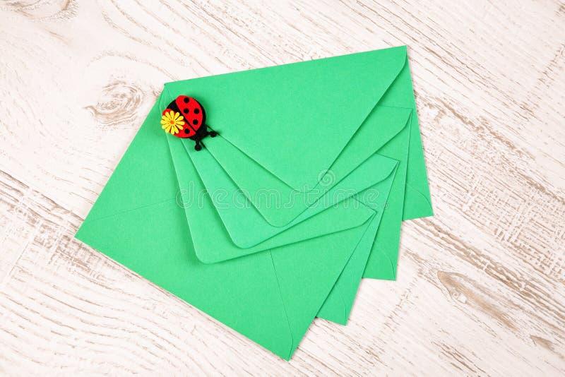 顶视图,四个绿色信封平的位置由被回收的纸制成,用瓢虫和花装饰,在白色木背景 免版税库存照片