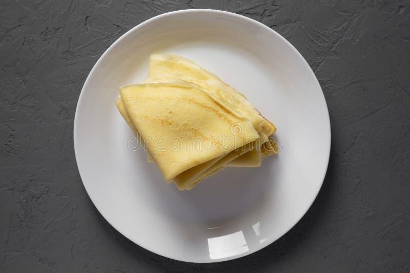 顶视图,堆在一块白色板材的鲜美俄式薄煎饼在灰色背景 r r 免版税库存照片