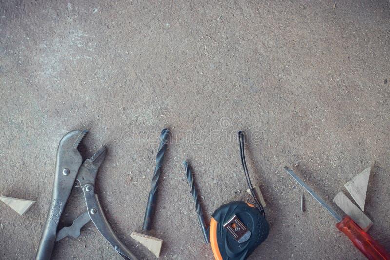 顶视图,木匠与许多工具的工作区域在多灰尘的水泥地板,工匠工具箱上 库存照片