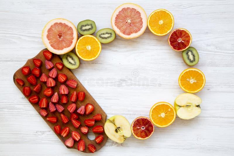 顶视图,葡萄柚,猕猴桃,苹果,草莓的五颜六色的果子样式,橙色在白色木背景 从上 免版税图库摄影