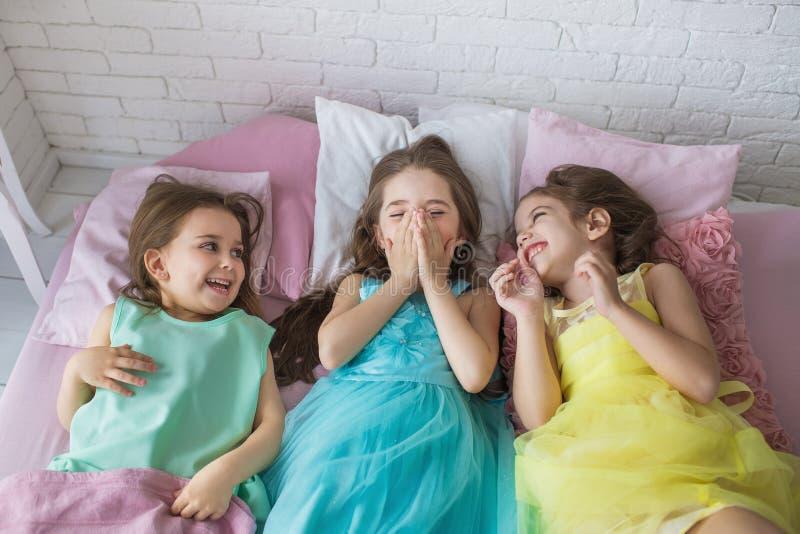 顶视图:三个相当小女孩在床上躺并且微笑 免版税库存照片