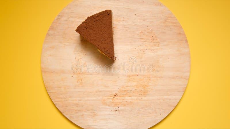 顶视图:巧克力蛋糕前个片断在黄色背景的 库存照片