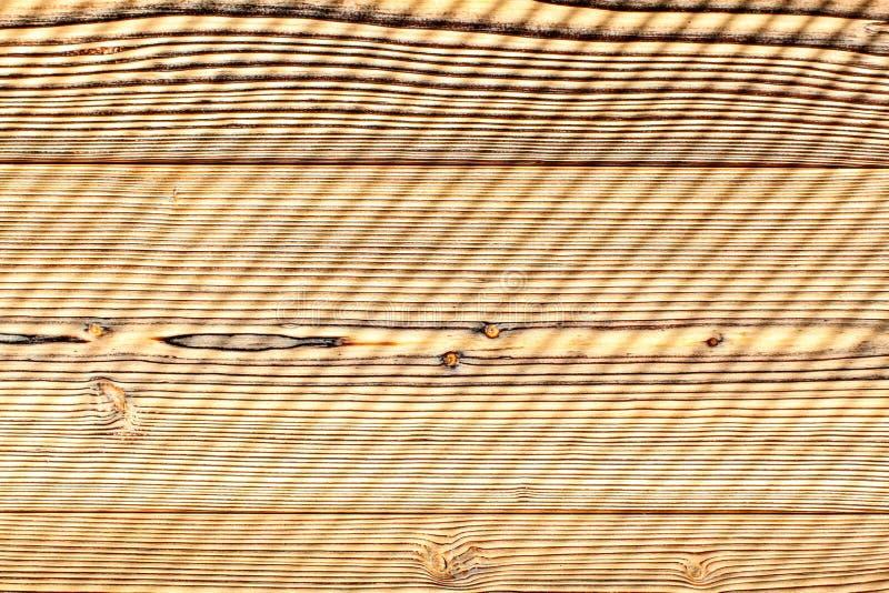 顶视图-书桌由早晨太阳之前点燃的木板,离开对角条纹样式的树荫做了 木抽象的背景 库存照片