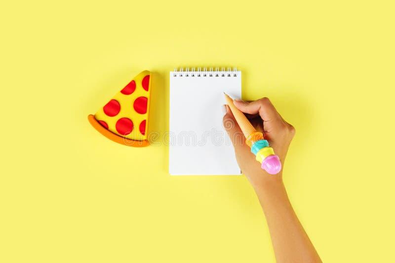 顶视图 使用笔的少妇的手为写在空白的笔记本 库存图片