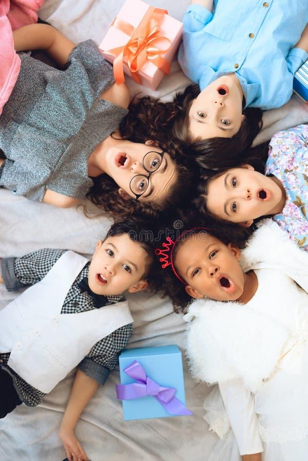 顶视图 在圈子形状的地板上说谎快乐的孩子的画象  免版税库存图片
