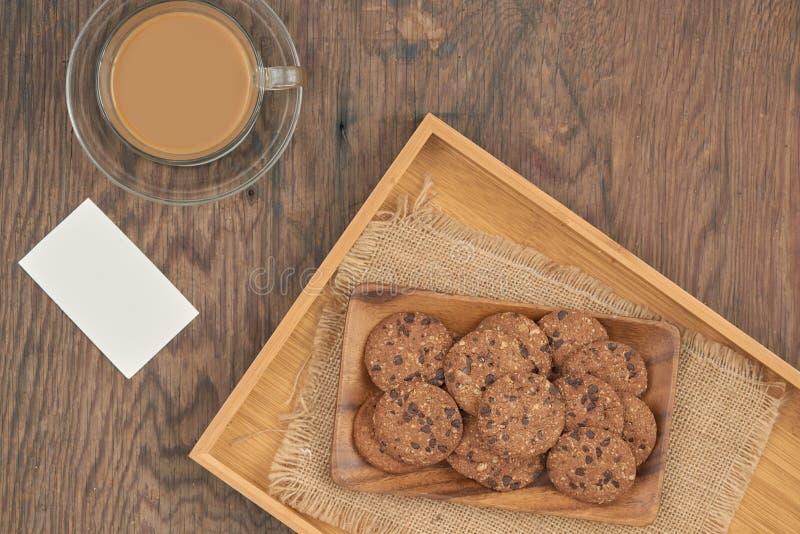 顶视图-在板材和一个杯子的巧克力曲奇饼在木桌上的牛奶咖啡与空插件 图库摄影