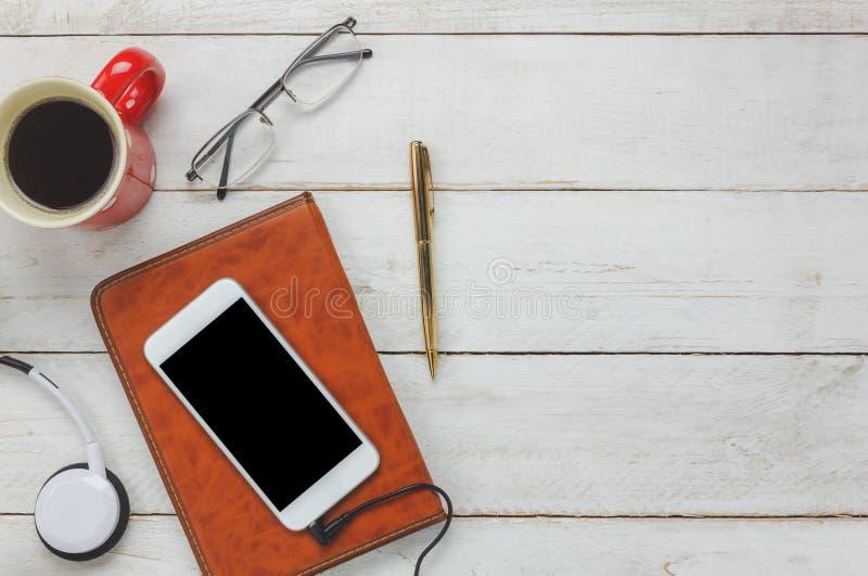 顶视图/平的位置笔/笔记本/白色手机/听的无线电音乐 免版税库存图片