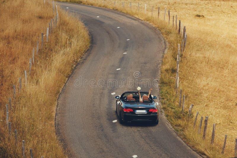 顶视图 愉快的已婚夫妇驾驶在一条乡下公路的一辆敞篷车汽车他们的蜜月的,新娘获得与ha的乐趣 免版税图库摄影