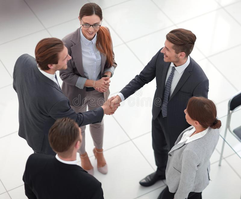 顶视图 握手贸易伙伴在办公室 库存照片