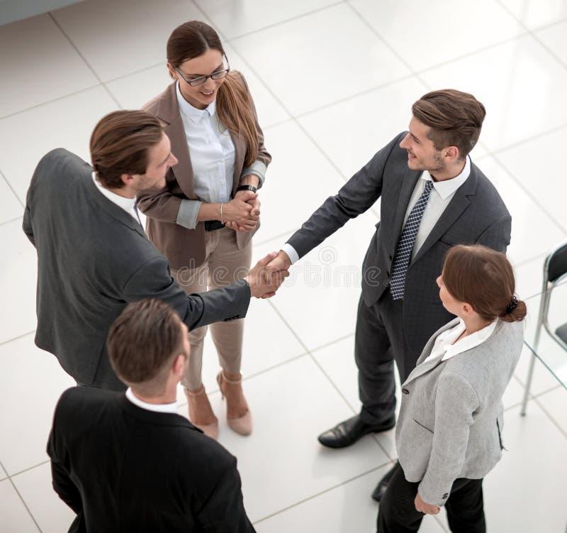 顶视图 握手贸易伙伴在办公室 免版税库存图片