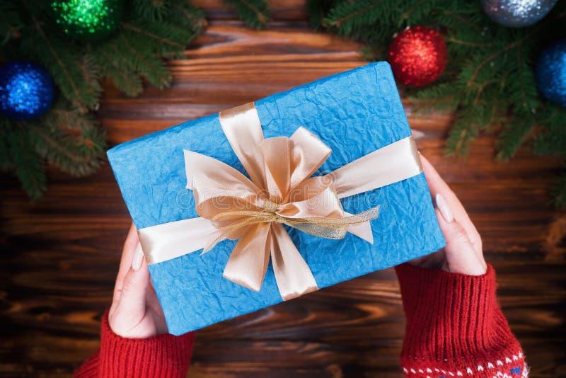 顶视图 有在与金黄丝带的蓝纸包裹的礼物的妇女的手 木葡萄酒桌 美好的假日 图库摄影