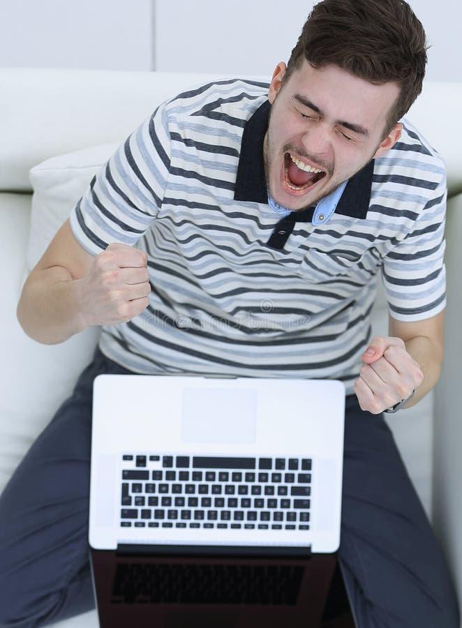 顶视图 有膝上型计算机的欢腾的年轻人坐长沙发 库存图片