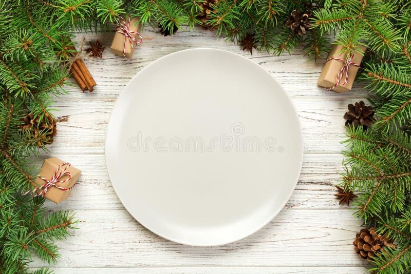顶视图 空的板材回合陶瓷在木圣诞节背景 假日晚餐与新年装饰的盘概念 免版税库存图片