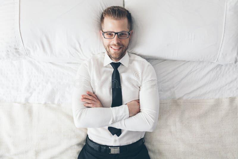 顶视图 戴说谎在床上的眼镜的英俊的商人 库存图片