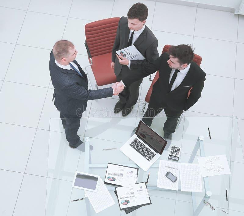 顶视图 财政伙伴握手在业务会议前的 免版税库存照片