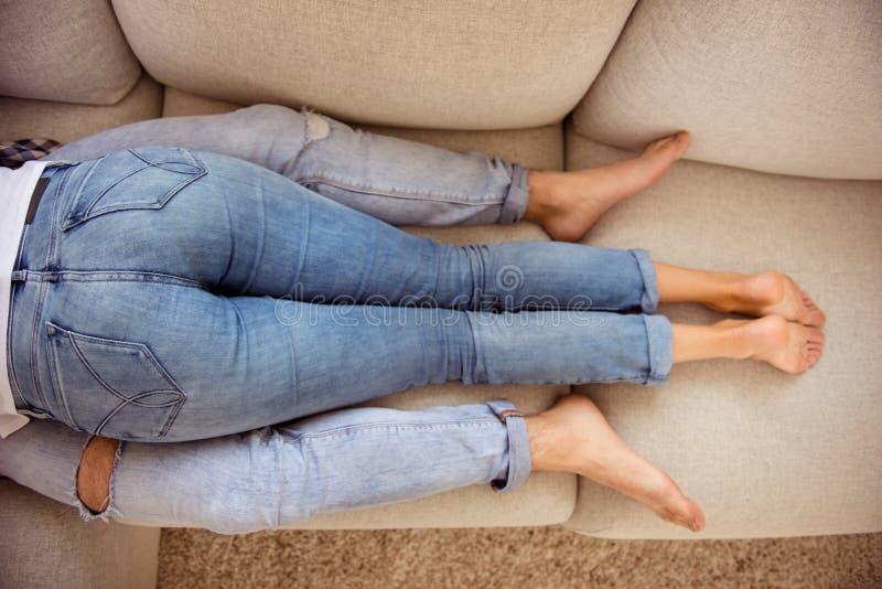 顶面上面大角度看法播种了有吸引力的好的微小的说谎在米黄舒适法院放松的适合稀薄的苗条腿夫妇 免版税图库摄影
