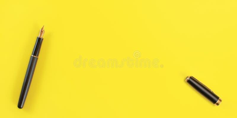 顶面下来视图-黑喷泉墨水笔用金鸟嘴,打开了,在右边的盖帽,黄色背景,文本的空间 免版税库存图片