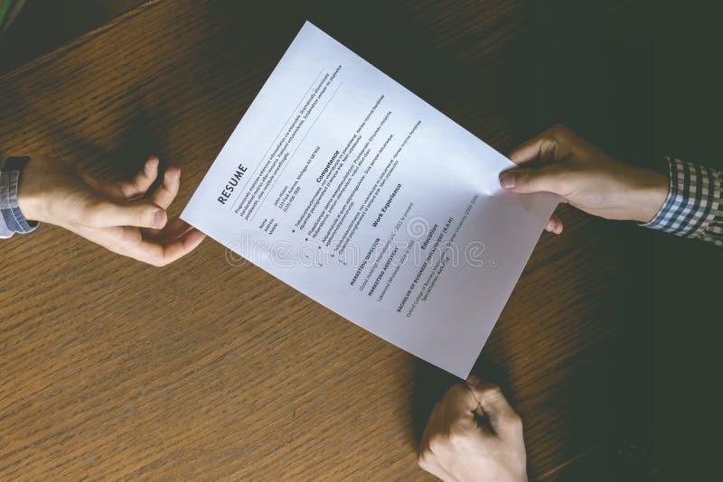 顶面天花板直接地上面观点的雇员聘用的人和审查在办公室桌上的简历 免版税库存图片