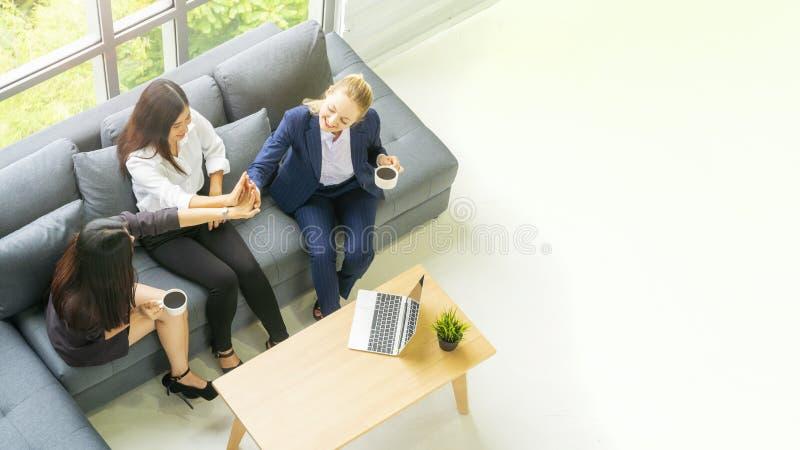 顶面鸟瞰图女商人谈话和坐灰色长凳沙发w 库存图片
