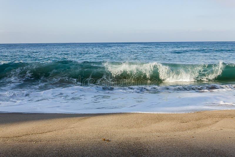 顶饰透明打破在沙滩的管波浪的Tourqouise与回流 免版税图库摄影
