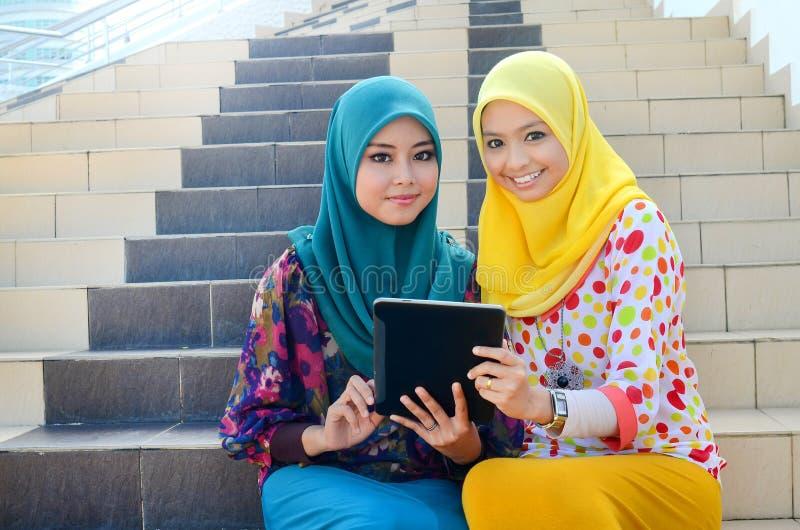 顶头围巾的年轻亚裔回教妇女一起微笑 免版税库存图片