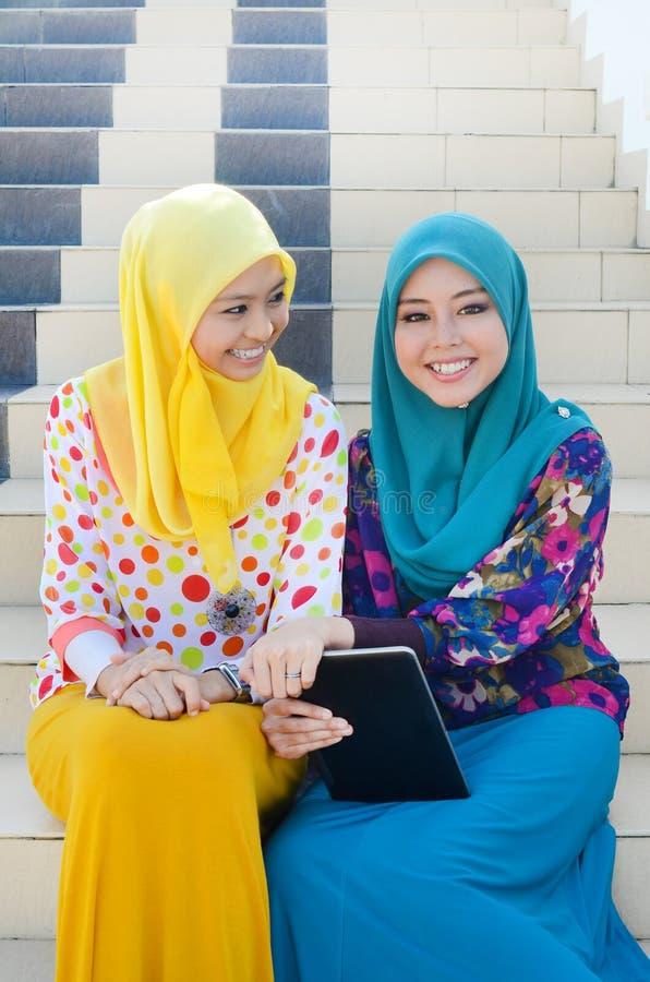顶头围巾的年轻亚裔回教妇女一起微笑 图库摄影