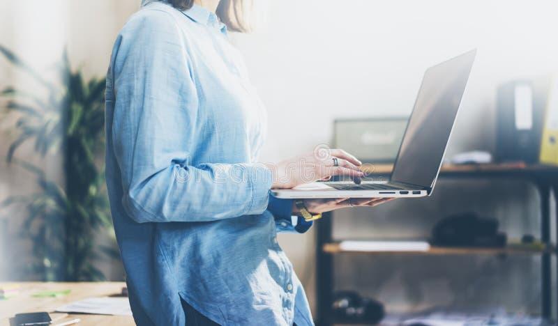 项目负责人运作的过程 照片年轻企业wooman与新的起动一起使用 握现代笔记本手 库存图片