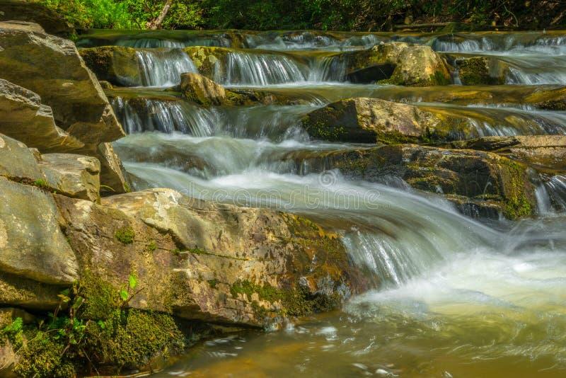顺流瀑布在岩石和冰砾 图库摄影