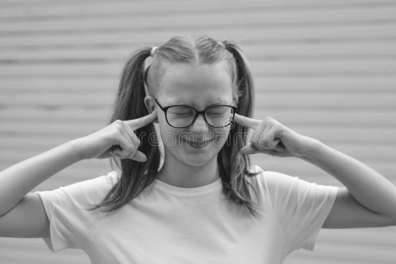 顽固的俏丽的孩子,青少年的年龄女孩,在巨大心情和显示她的微笑和长发尾巴 r 免版税库存照片