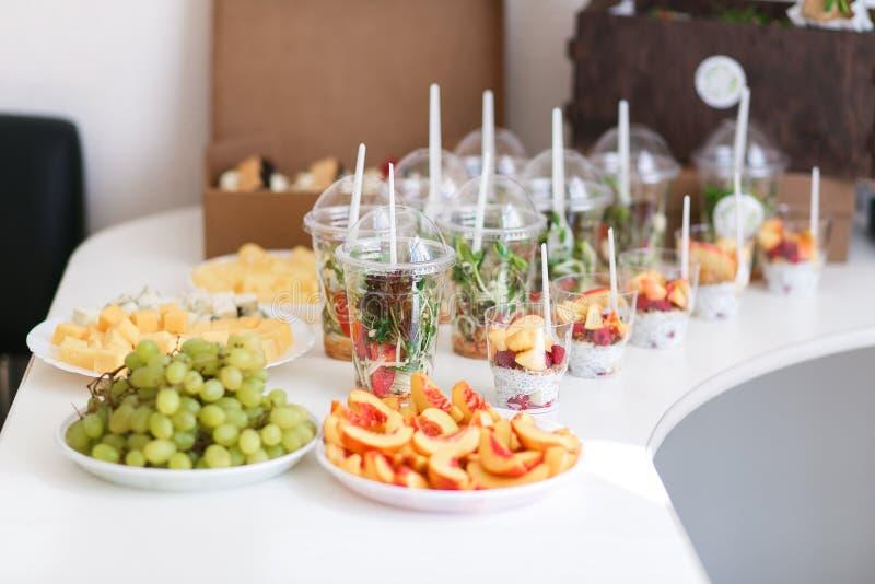 顾及婚礼聚会 大量混杂的各种各样的种类切的果子,菜,乳酪,在塑料杯子的沙拉  免版税库存照片